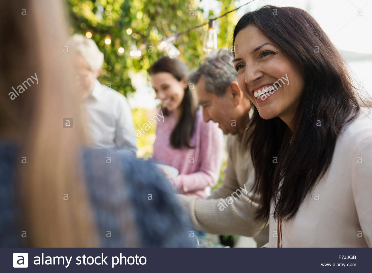 Smiling woman talking at social gathering - Stock Image