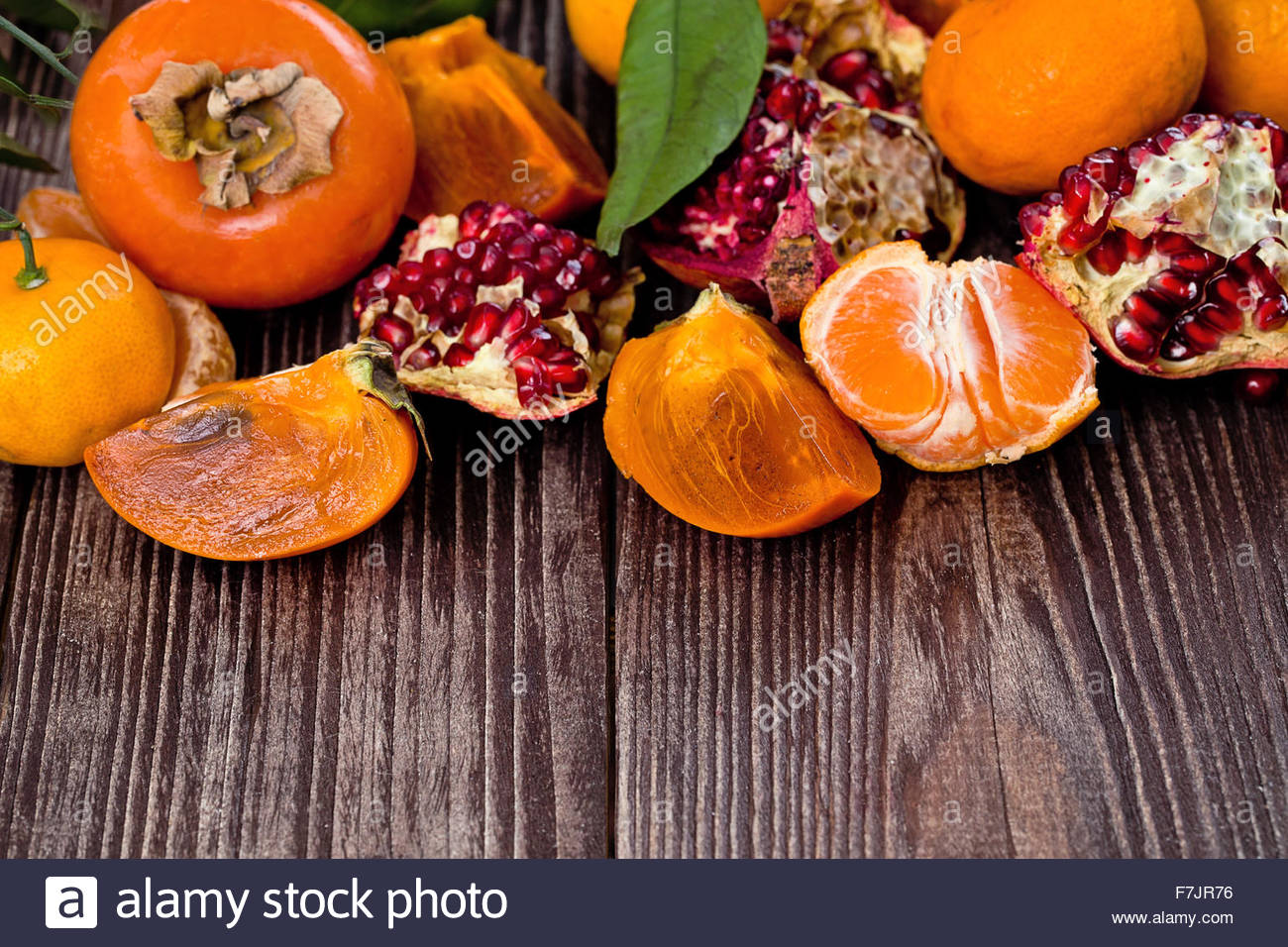 Fresh fruits on a wooden background. Raw and vegetarian eating frame. Sliced orange, persimmon, tangerine, pomegranate. - Stock Image