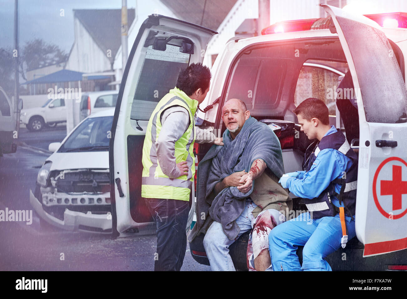 Rescue workers tending to car accident victim at back of ambulance - Stock Image