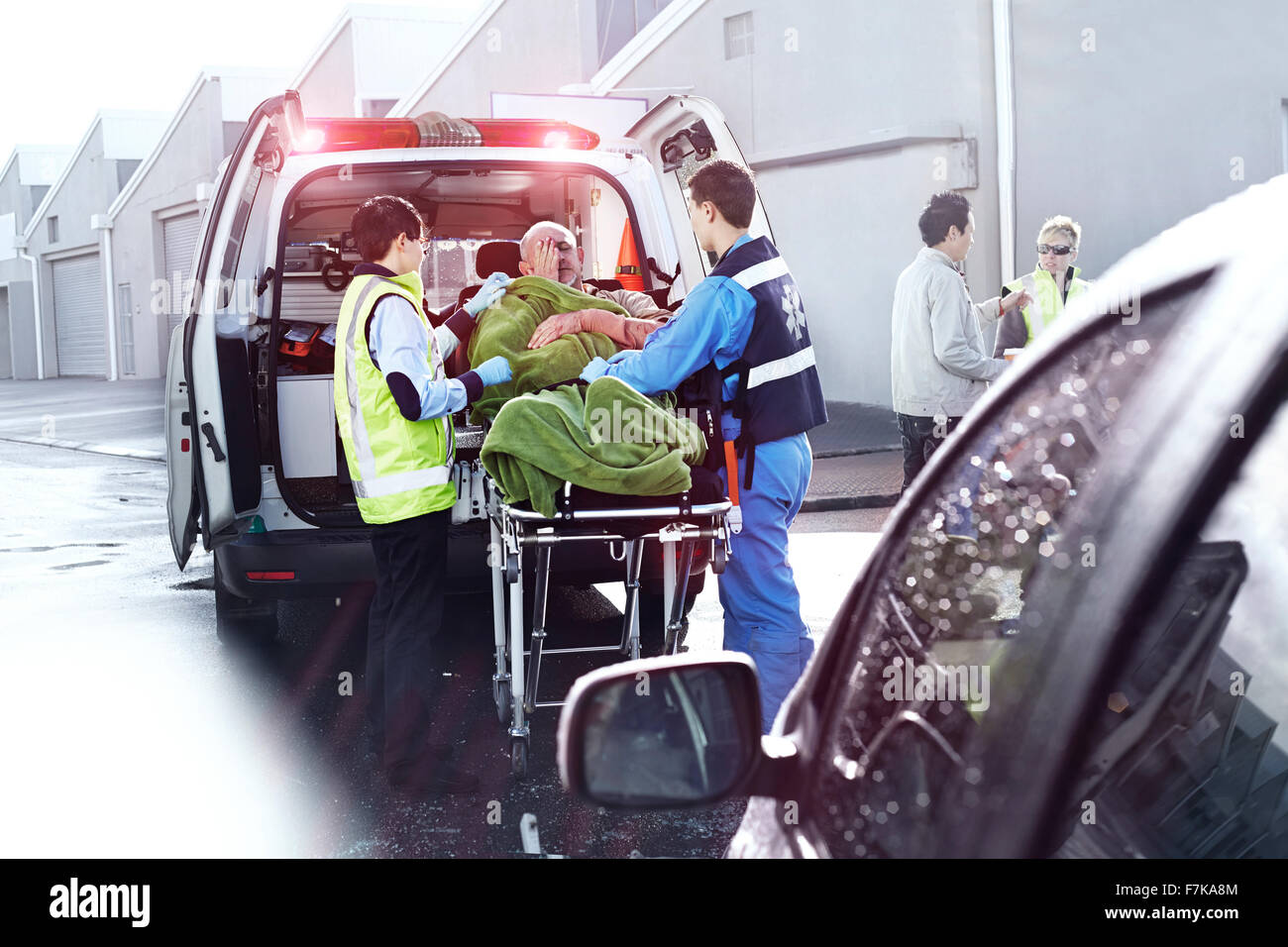 Rescue workers tending to car accident victim on stretcher at back of ambulance - Stock Image