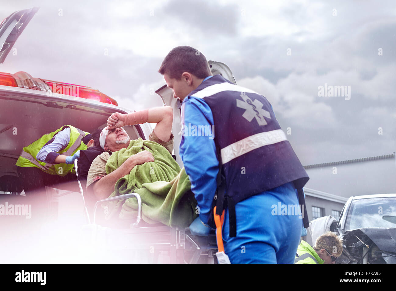 Rescue workers loading car accident victim into back of ambulance - Stock Image