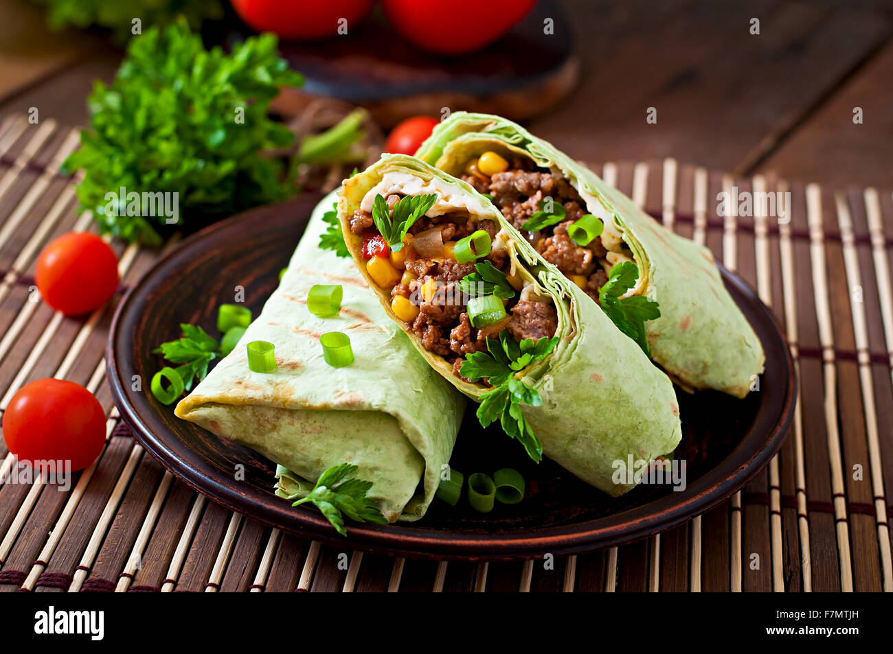 Burritos wraps with minced beef and vegetables on a wooden background - Stock Image