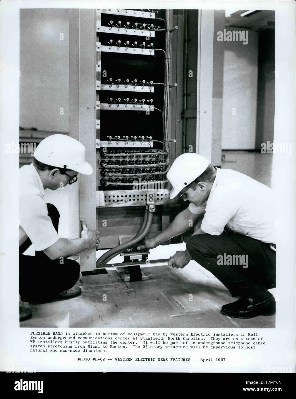 1972 - Flexbile Band is attached to bottom of equipment bay by Western Electric Installers in Bell System underground - Stock Image