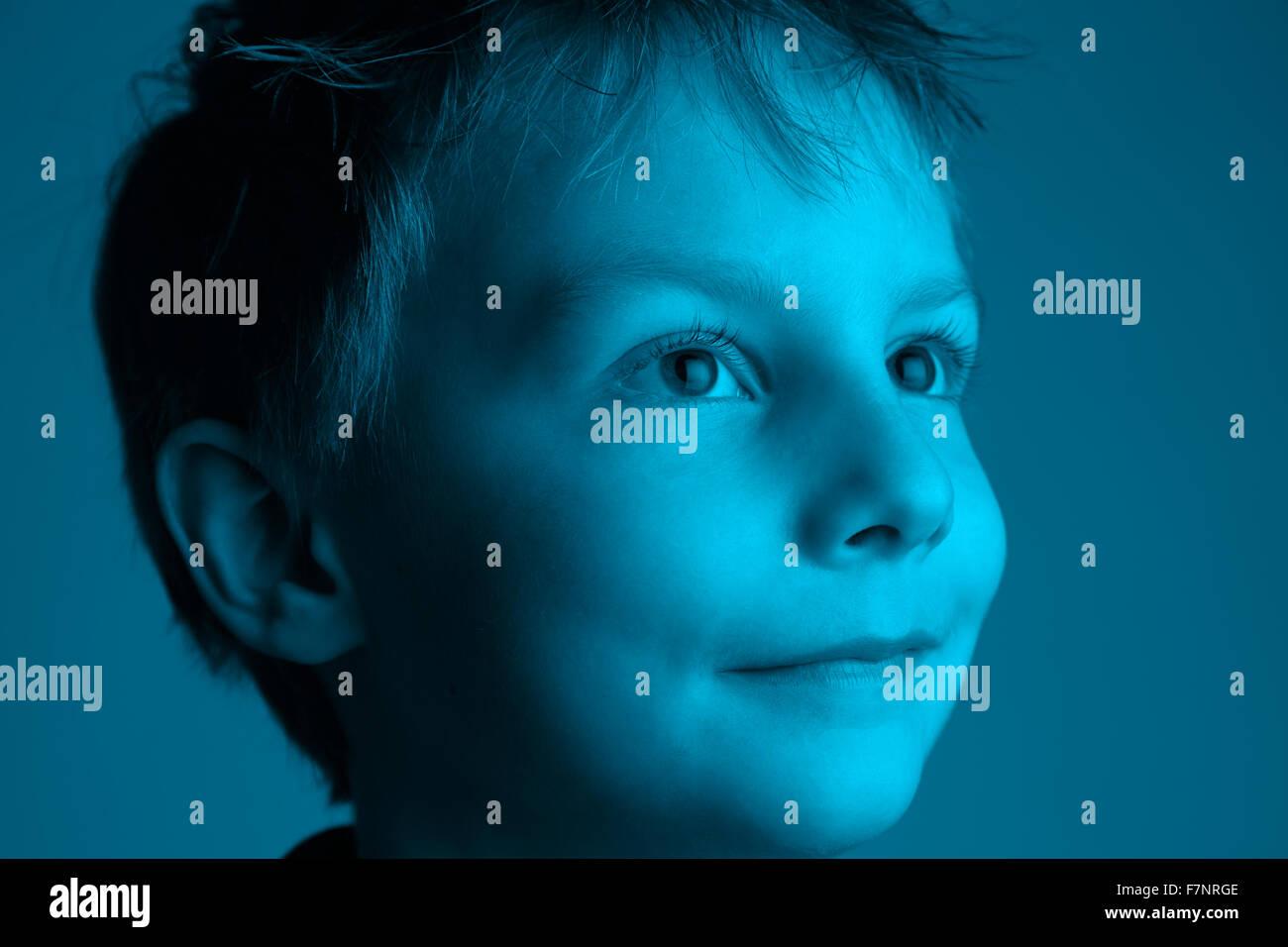 Big expectation - big eyes: eight year old boy looking towards the light - Stock Image