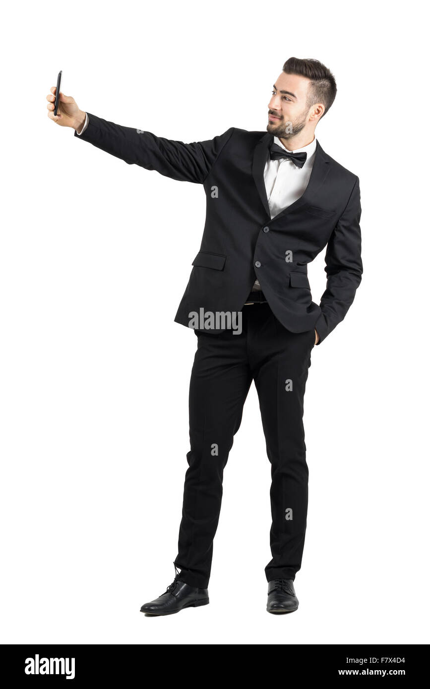 Young man in suit with bow tie taking selfie with cellphone. Full body length portrait isolated over white studio Stock Photo