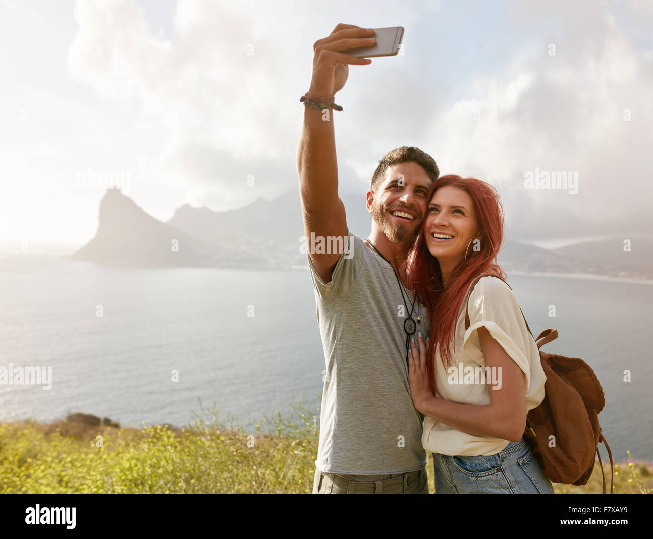 Cheerful young couple on holidays making selfie with smart phone. Young couple by the bay taking a selfie portrait - Stock Image
