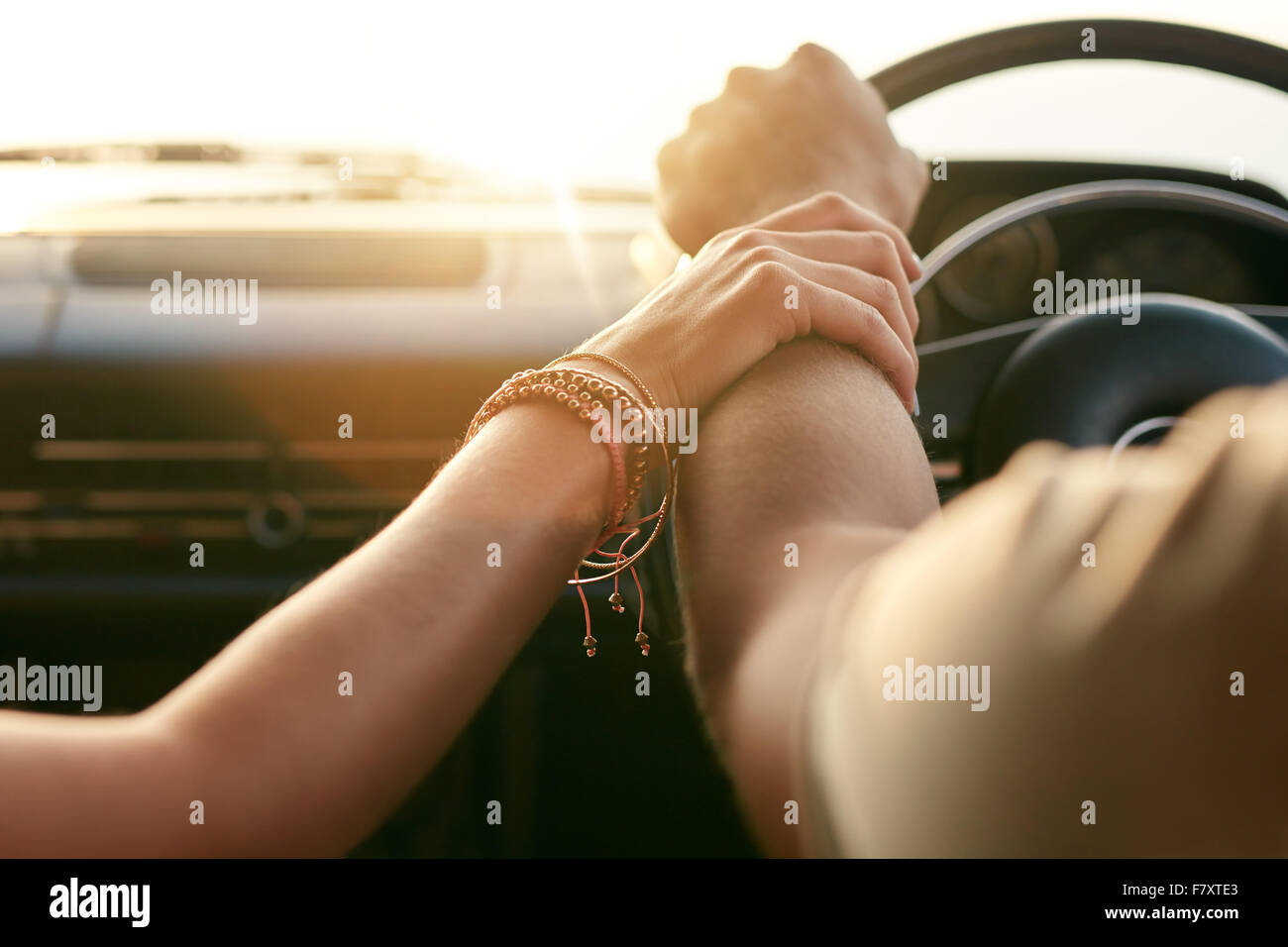 Close up shot of loving couple traveling by car and holding hands. Focus on hands of man and woman in a road trip. - Stock Image