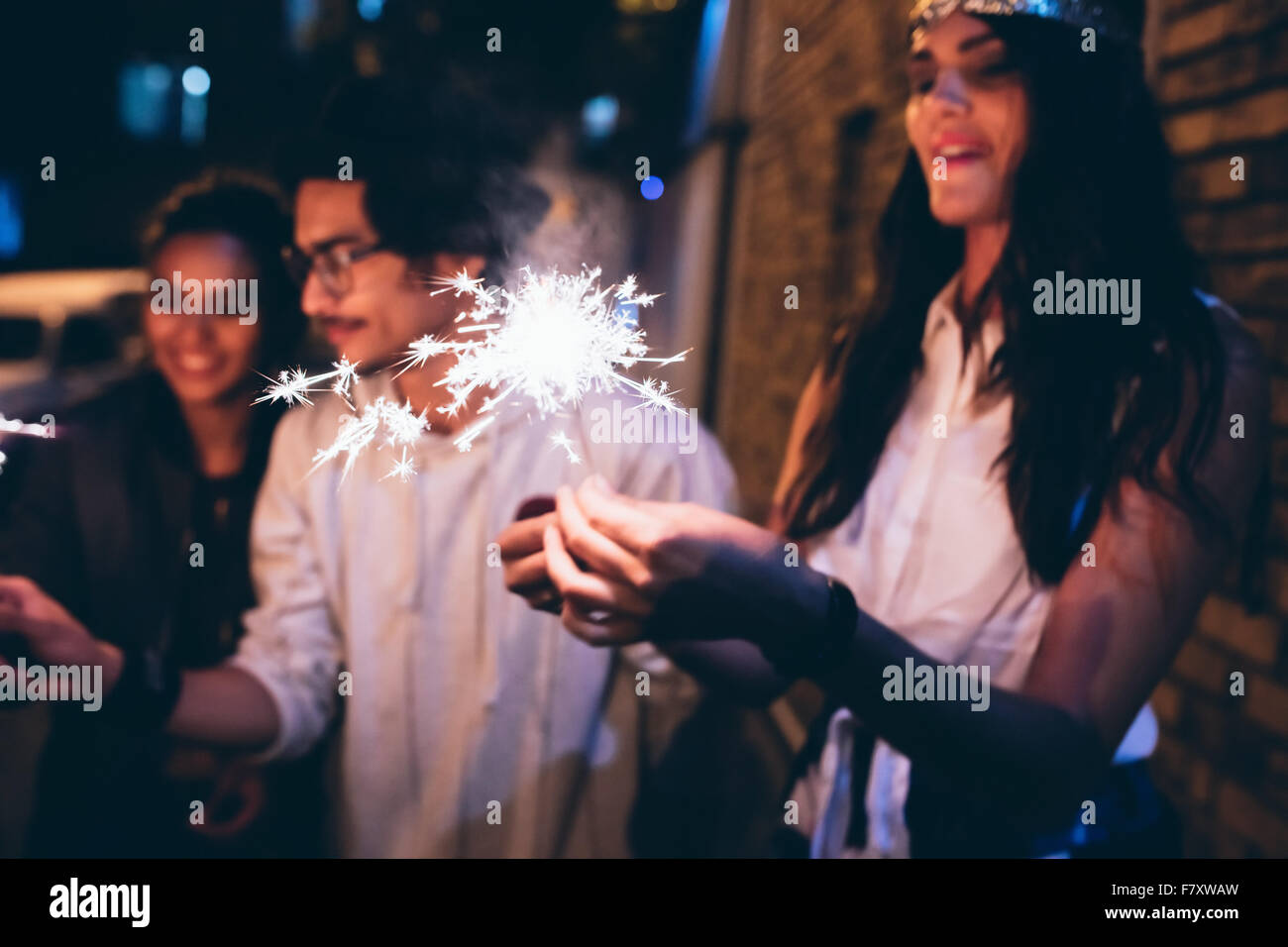Young friends out at night, celebrating with sparklers. Men and women hanging out at night having a party. - Stock Image