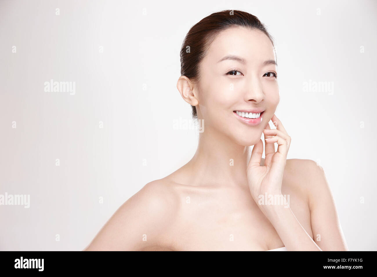 A woman touching her face - Stock Image