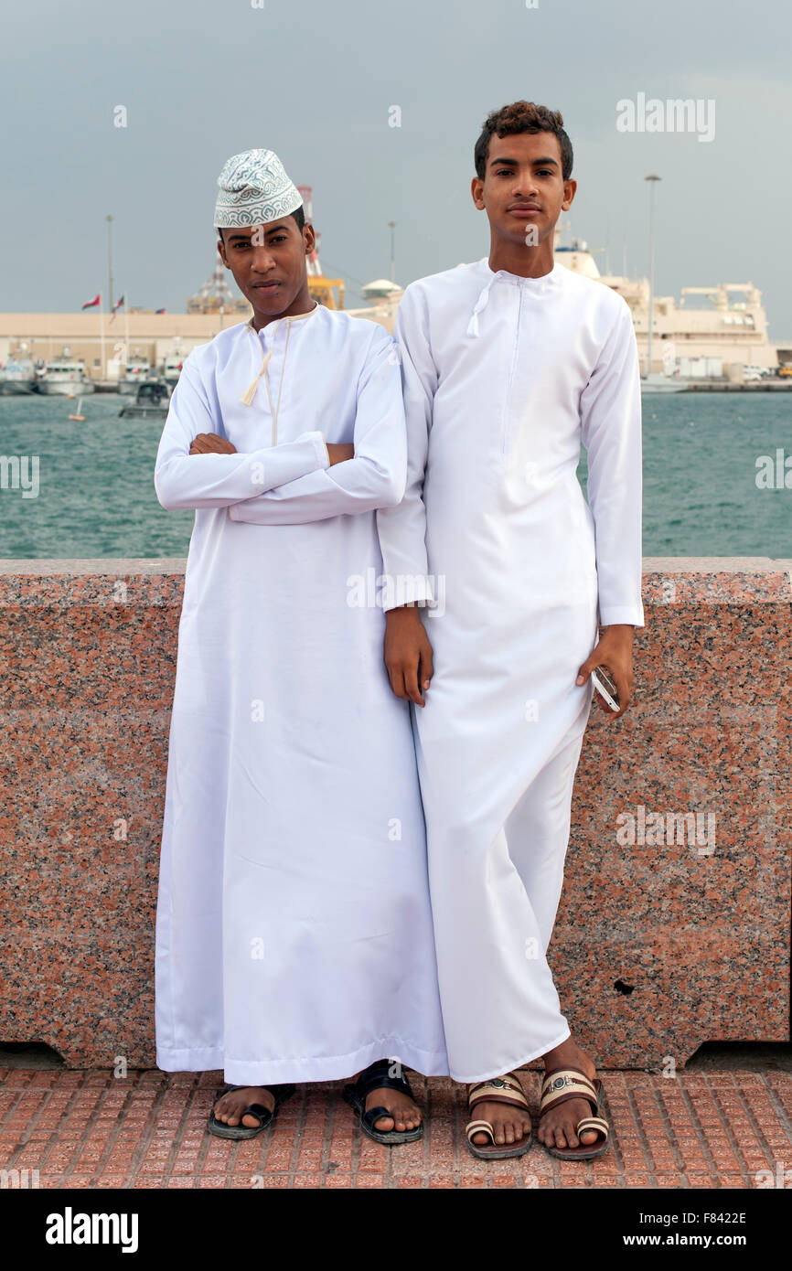 Young Omani men in traditional outfits on the Mutrah promenade in Muscat, the capital of the Sultanate of Oman. - Stock Image