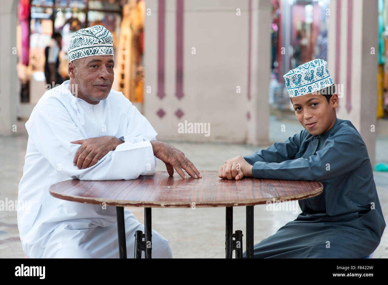 Omani man and his son sitting outside the Mutrah souk in Muscat, the capital of the Sultanate of Oman. - Stock Image