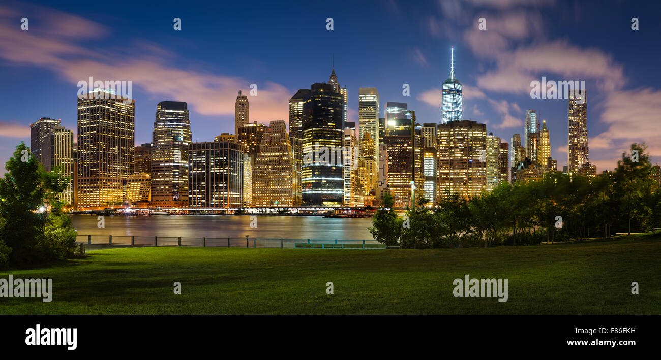 Evening view of Lower Manhattan illuminated skyscrapers across Brooklyn Bridge Park. Manhattan Financial District, - Stock Image