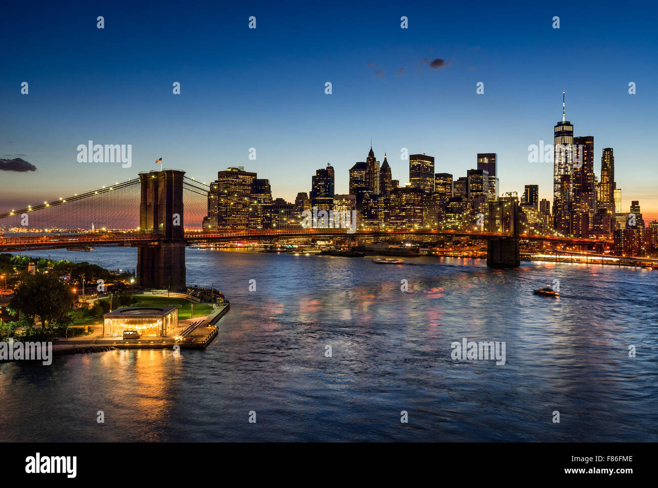 Brooklyn Bridge and illuminated Lower Manhattan at twilight. Financial District skyscrapers reflect in the East - Stock Image