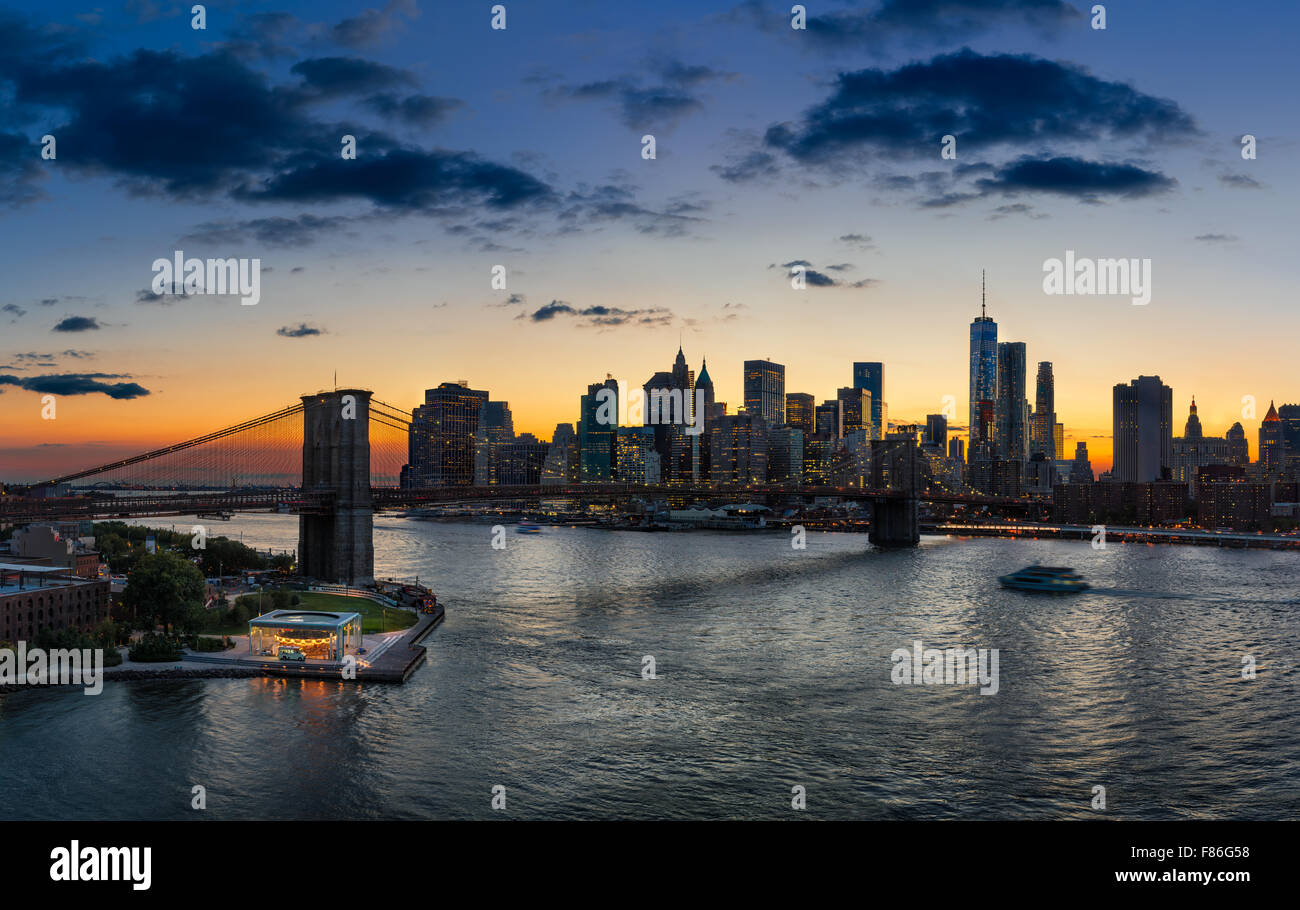 Elevated view of Brooklyn Bridge, East River, Lower Manhattan, skyscrapers and clouds at sunset. New York City - Stock Image