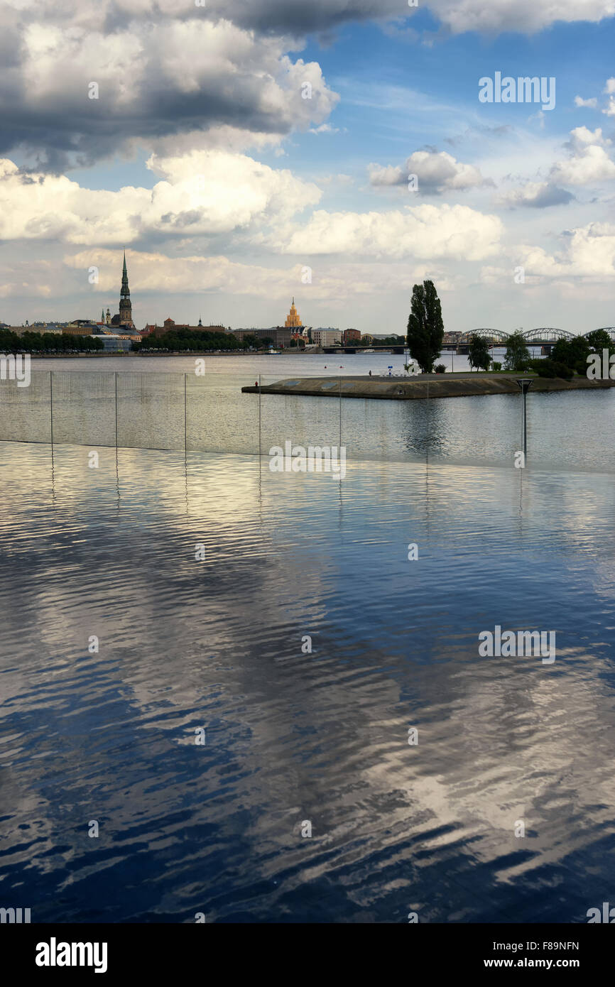 Cathedrals and railway bridge in Riga on the Daugava River in the summer sunny day with clouds reflection in the - Stock Image