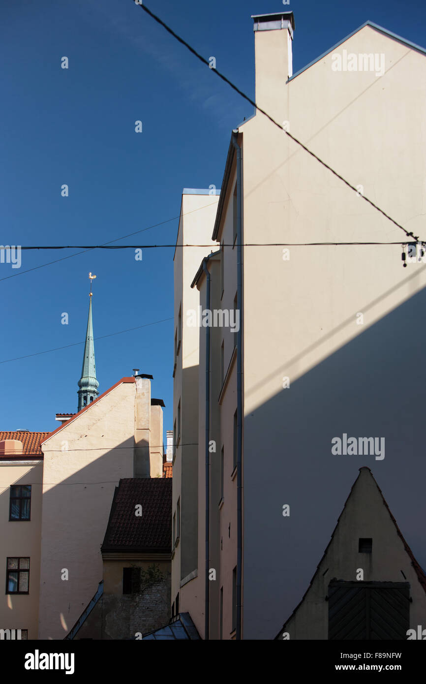 The geometry of the facades of old houses in the old city on the background of blue sky in Riga on a sunny summer - Stock Image
