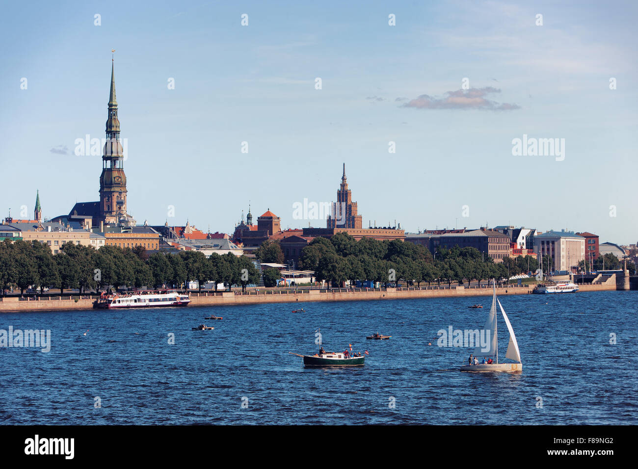 View of the city of Riga on the Daugava river with yachts and ships at the background of the spiers of churches - Stock Image