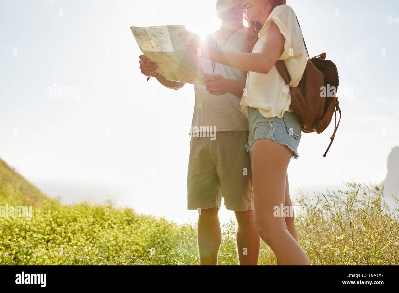 Young couple looking at map while standing outdoors in countryside with bright sunshine from behind. Couple looking - Stock Image