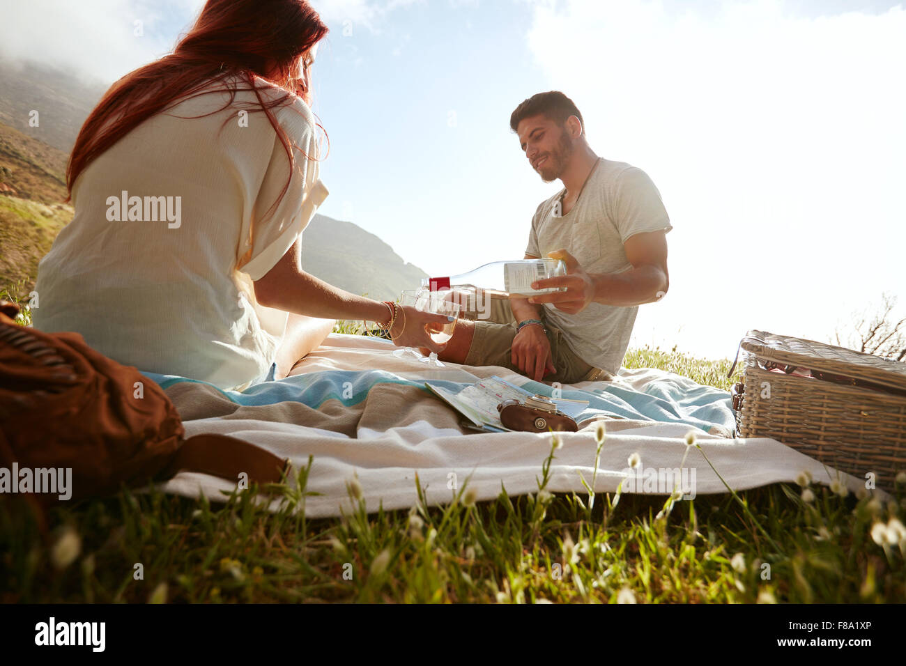 Young man pouring wine in glasses while sitting with his girlfriend. Young couple drinking wine and enjoying a picnic - Stock Image