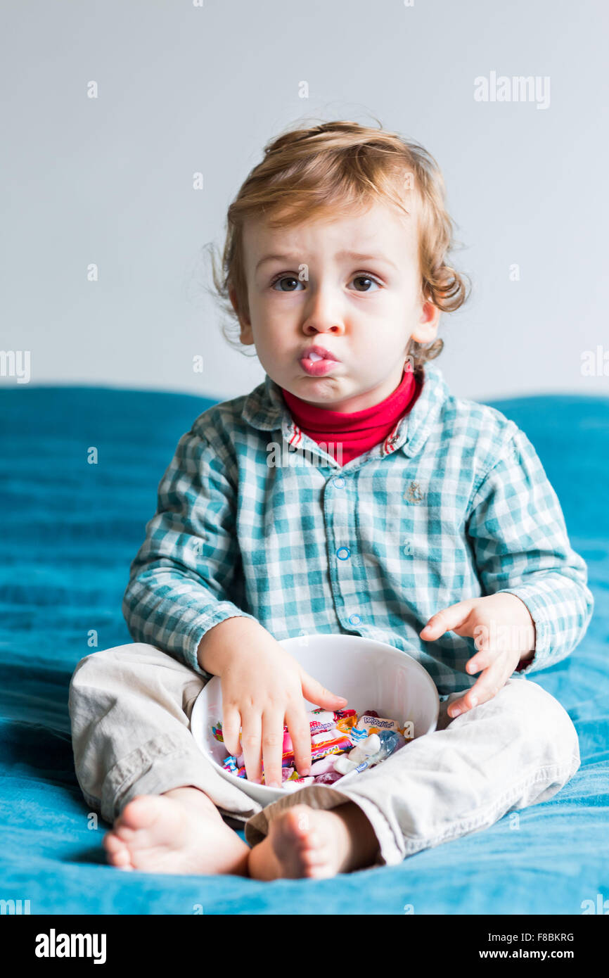 2 year-old boy eating sugary sweets. - Stock Image