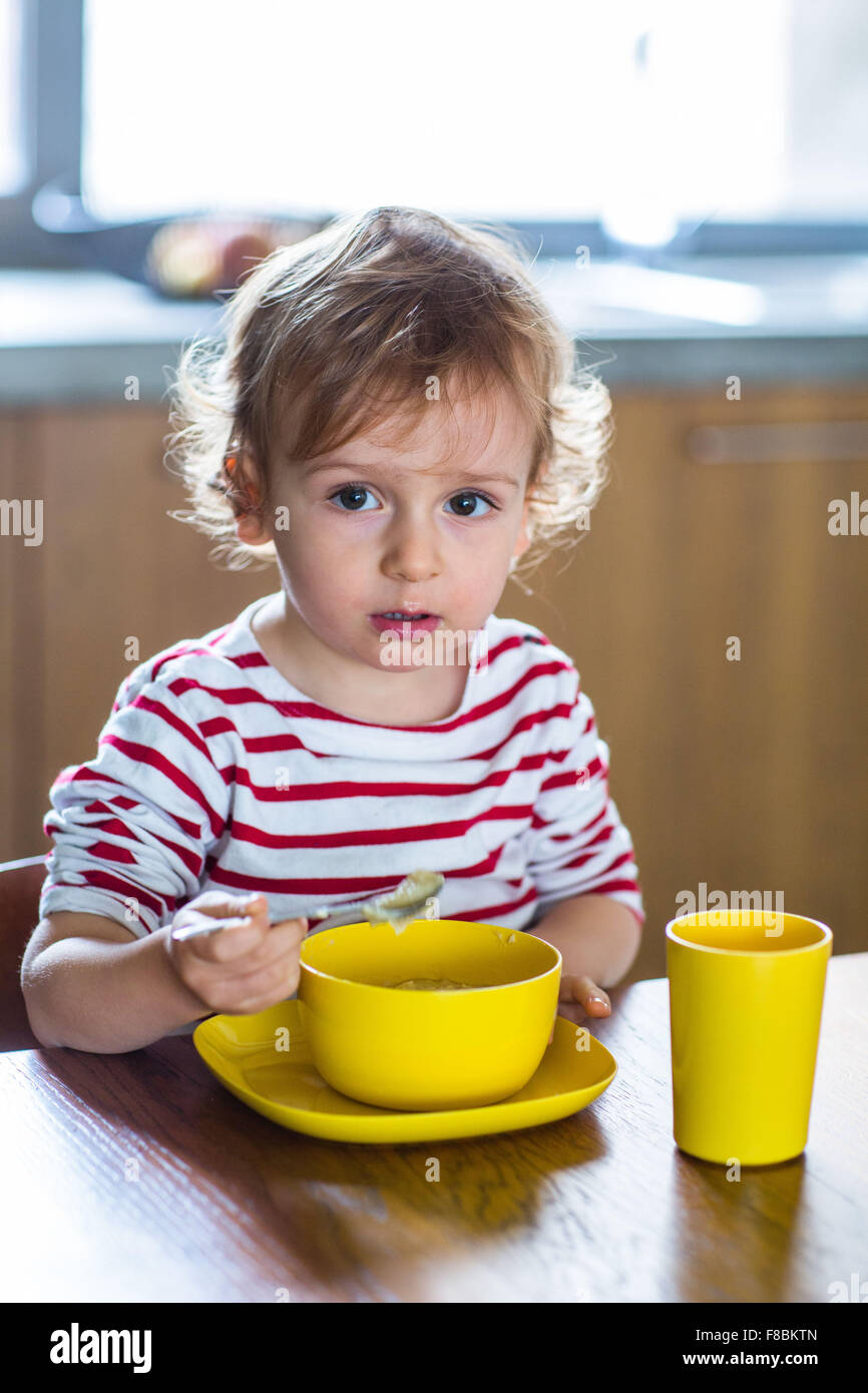 24 month old baby girl eating alone. Independence training. - Stock Image