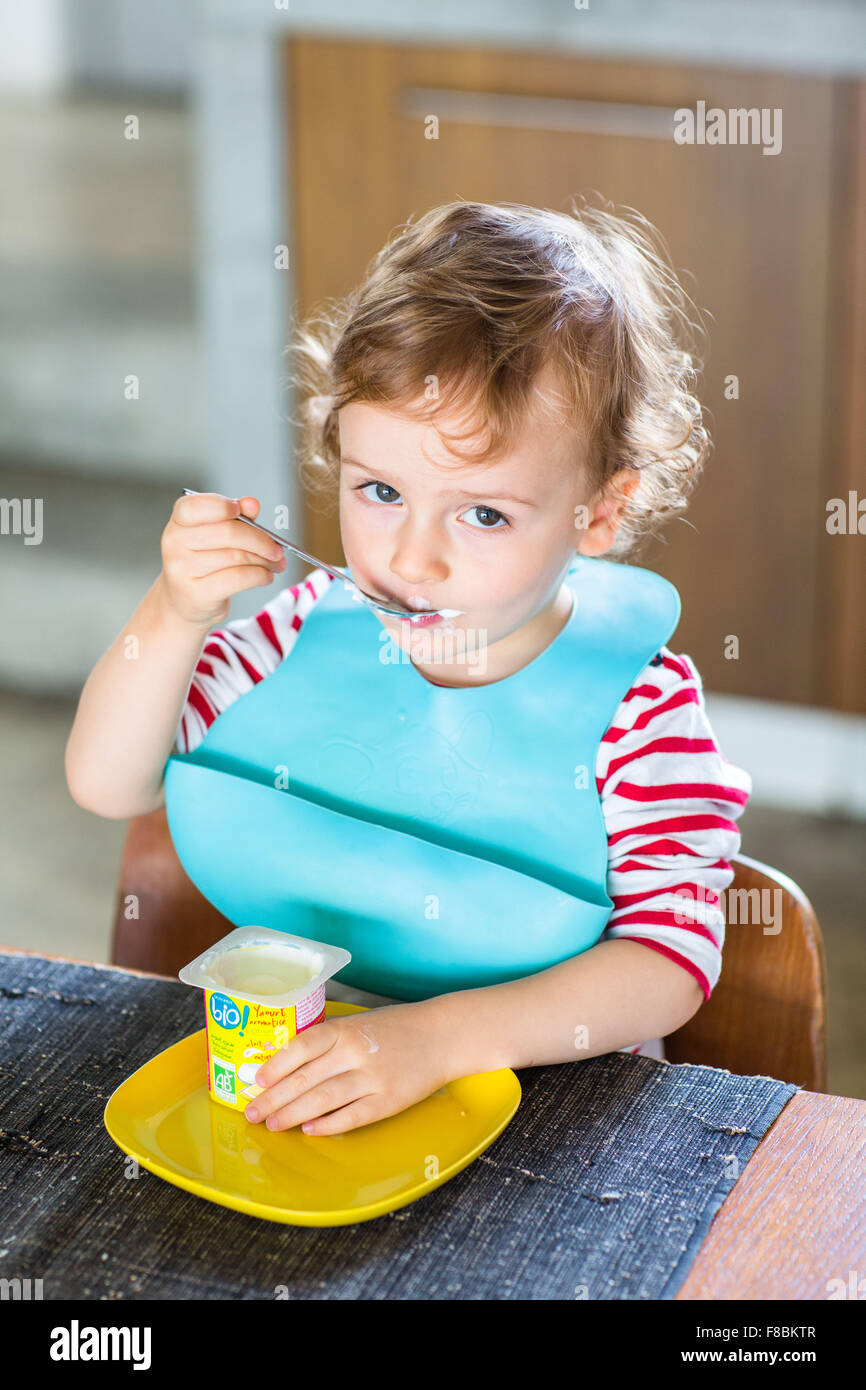 2 year-old boy eating a yoghurt. - Stock Image