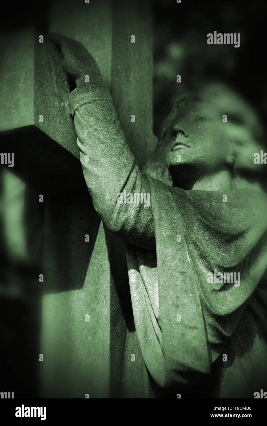 angel holding on to cross - Stock Image