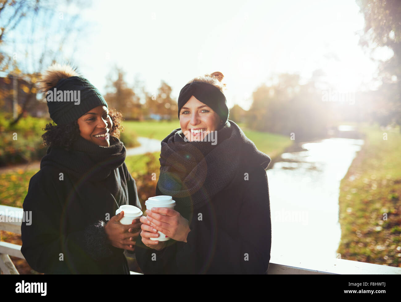 Two girlfriends looking at camera and smiling while standing on bridge, holding coffee to go, river on background - Stock Image