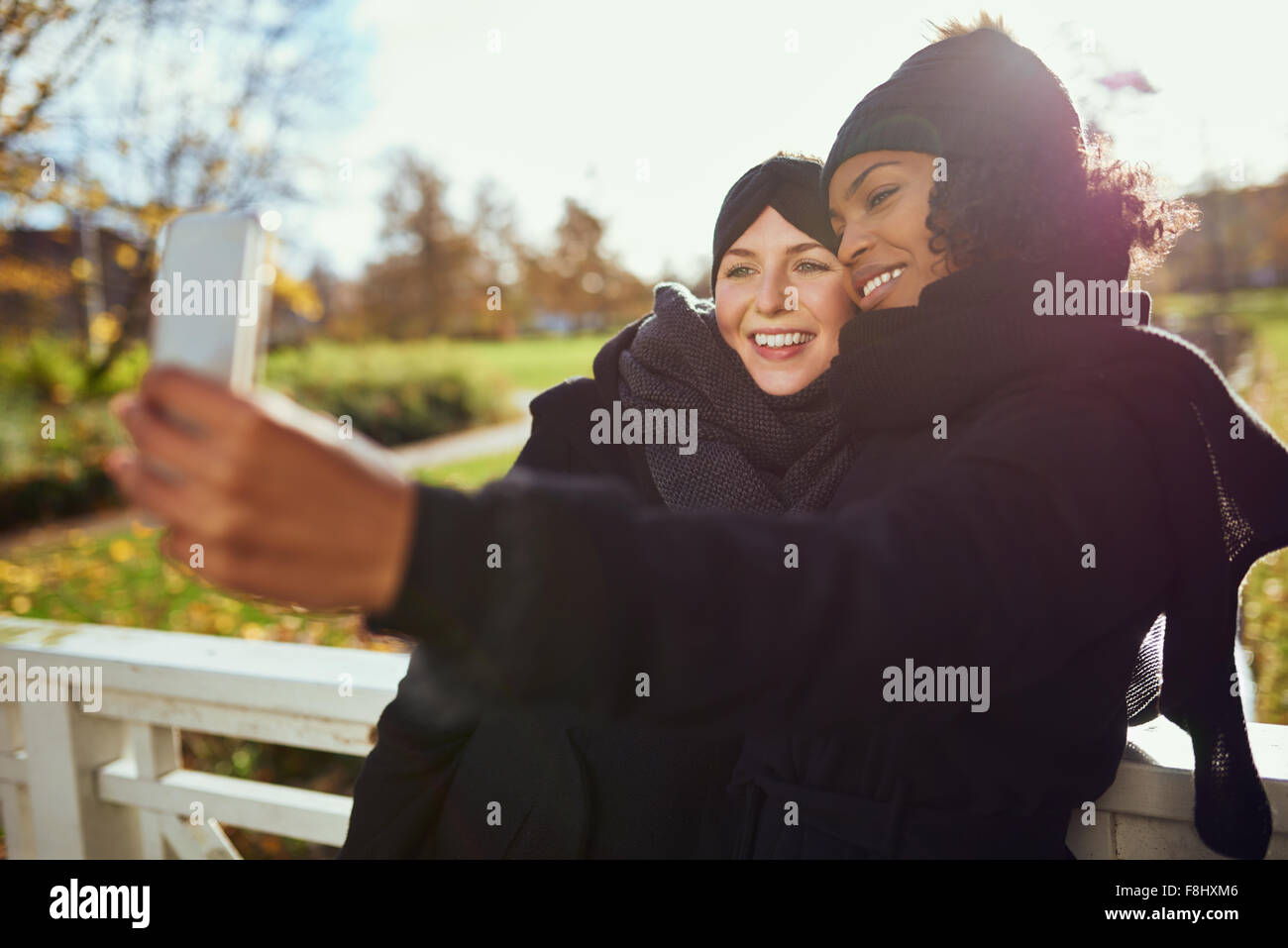 Two smiling young women in warm clothes taking selfie against of autumnal park - Stock Image