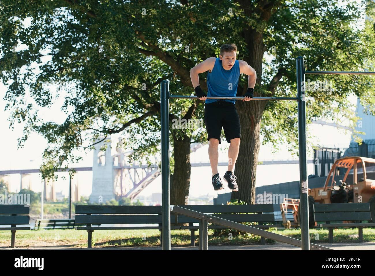 Young man exercising, using bar - Stock Image