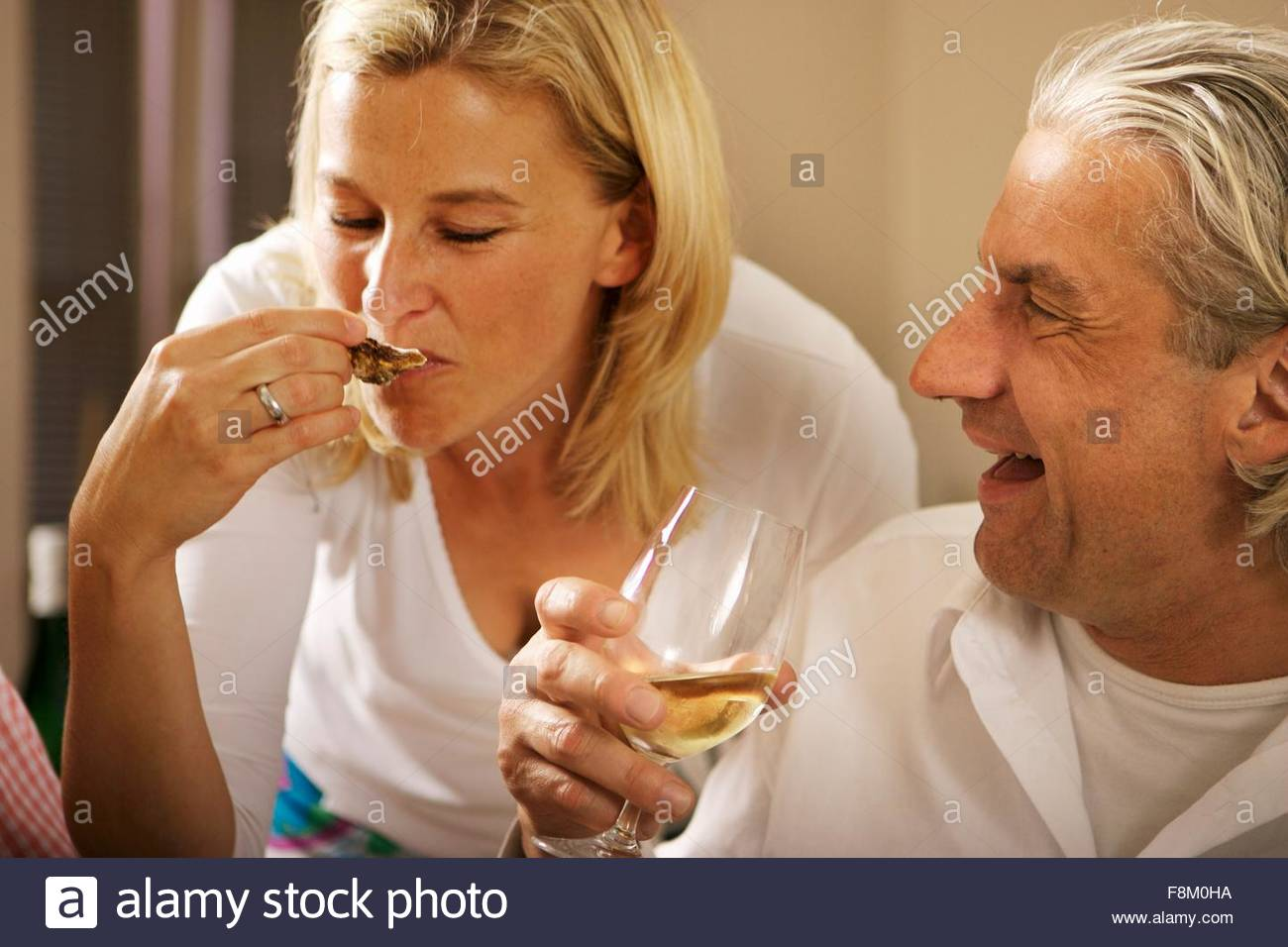 Blond woman and grey-haired man at a party - Stock Image