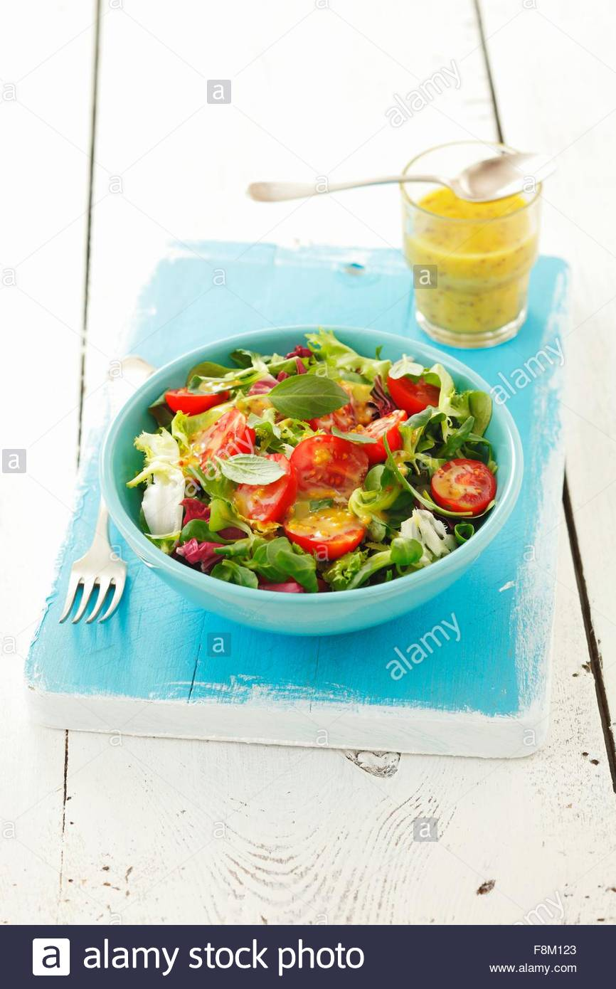 Salad leaves with cherry tomatoes and honey & mustard dressing - Stock Image