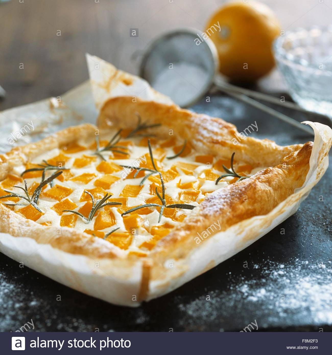 Quark and pumpkin tart with rosemary on baking parchment - Stock Image
