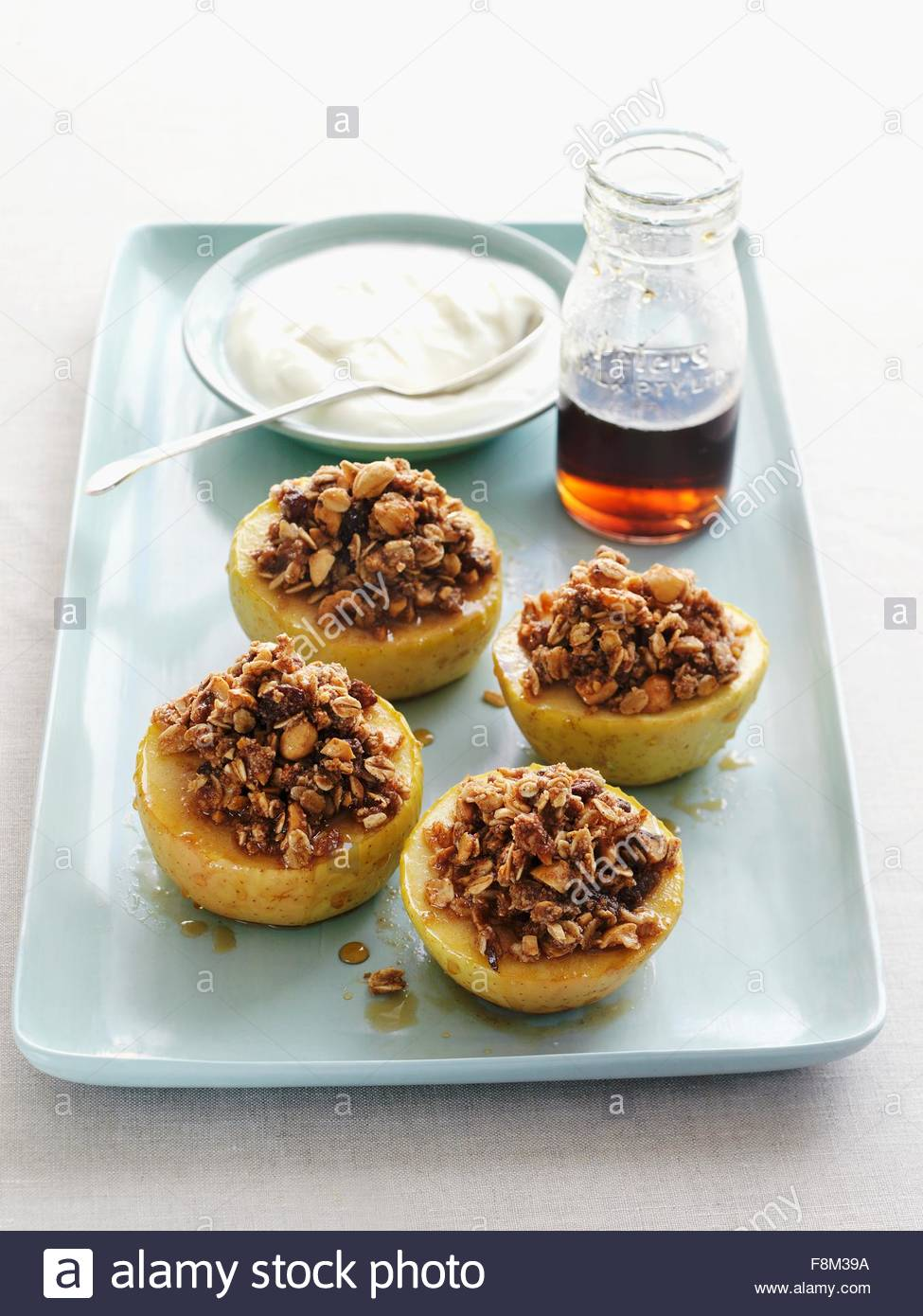 Stuffed baked apples, cream and maple syrup - Stock Image