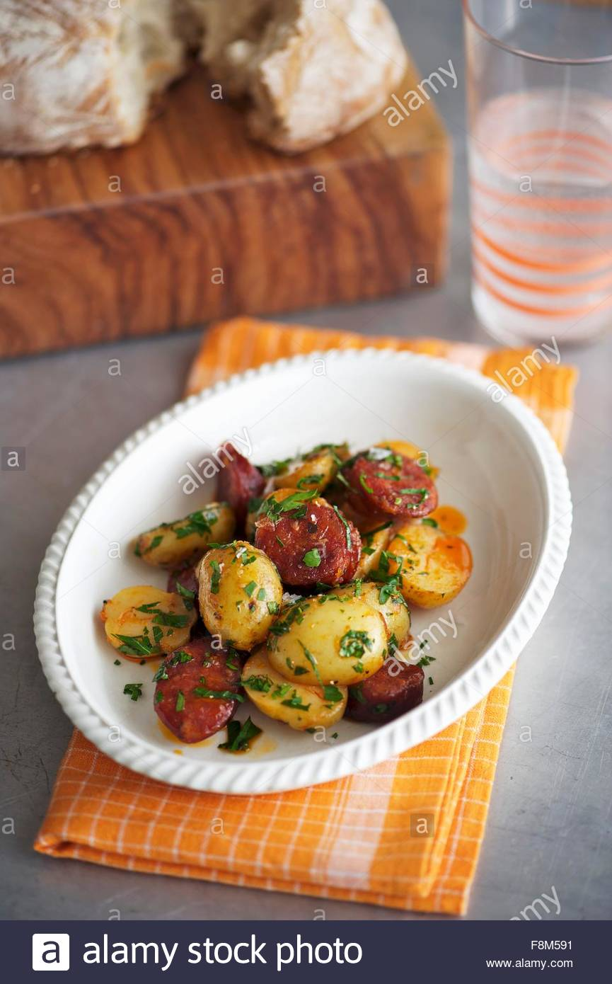 Potatoes with chorizo and parsley - Stock Image