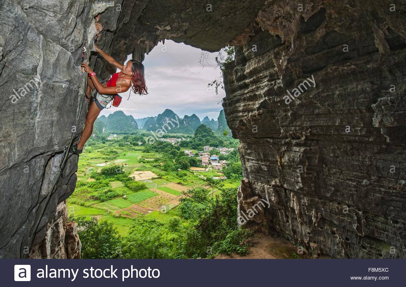 Female climber at treasure cave in Yangshuo, Guangxi Zhuang, China - Stock Image