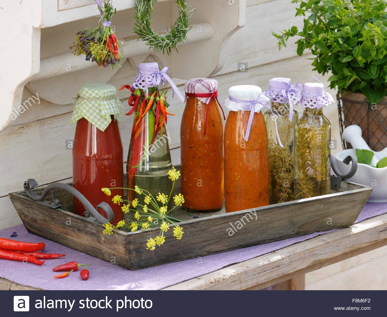Home-made tomato pesto and chilli-, thyme- and rosemary vinegar - Stock Image