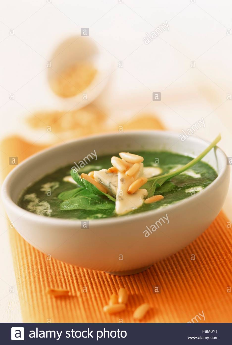Spinach soup with blue cheese and pine nuts - Stock Image