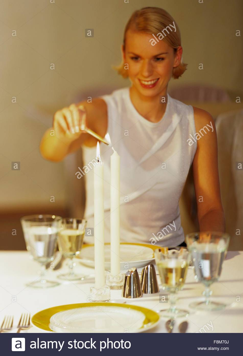 A young woman lighting a candle on a laid table - Stock Image