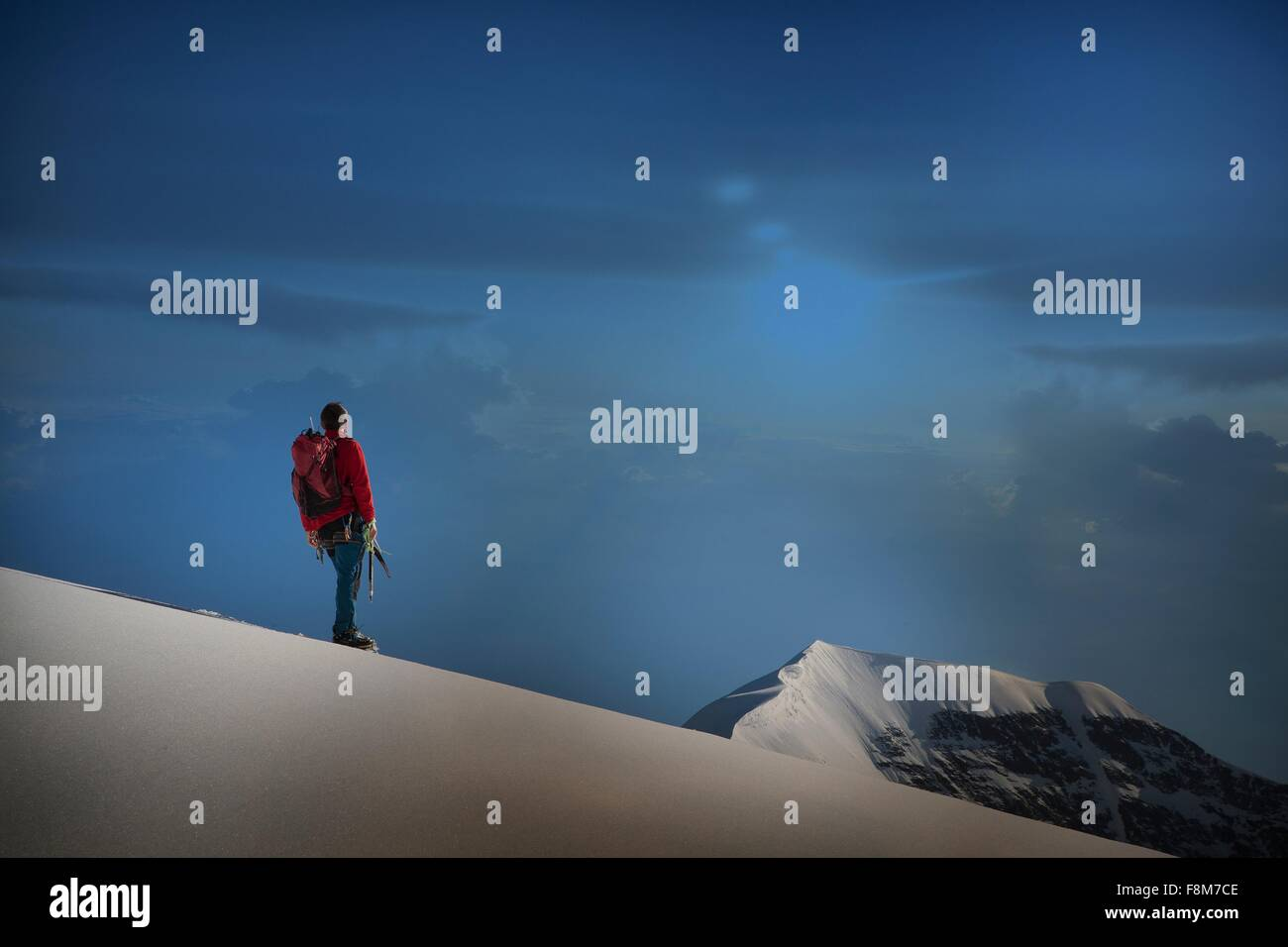 Male climber standing on ridge looking out,  Canton Bern, Switzerland - Stock Image