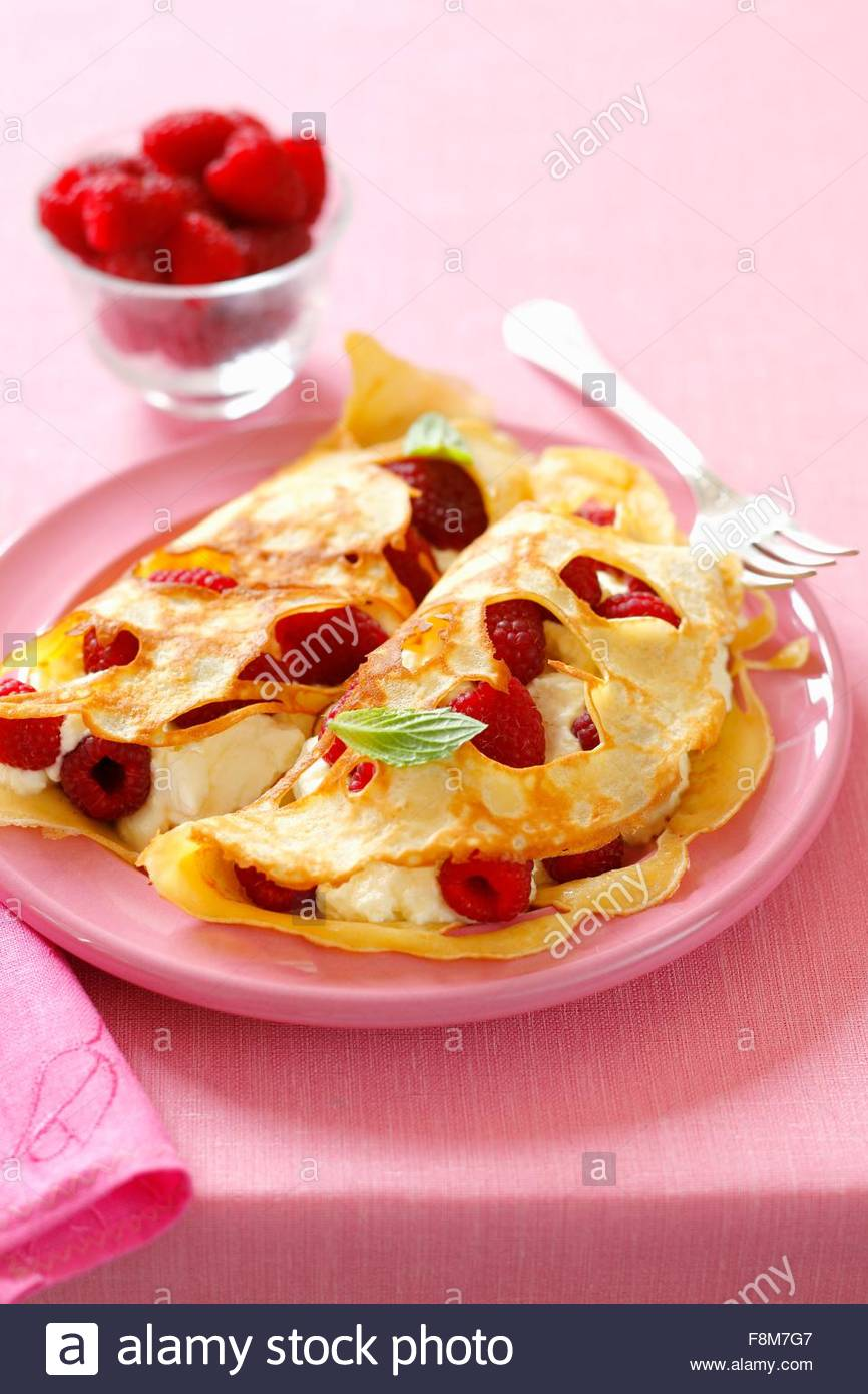 Holey pancakes with raspberries and cream - Stock Image
