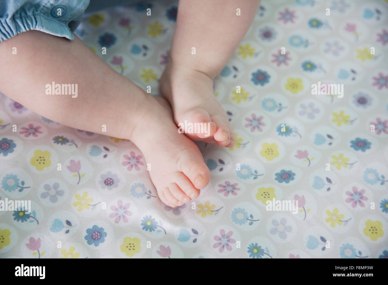 Baby girl lying down, focus on feet - Stock Image