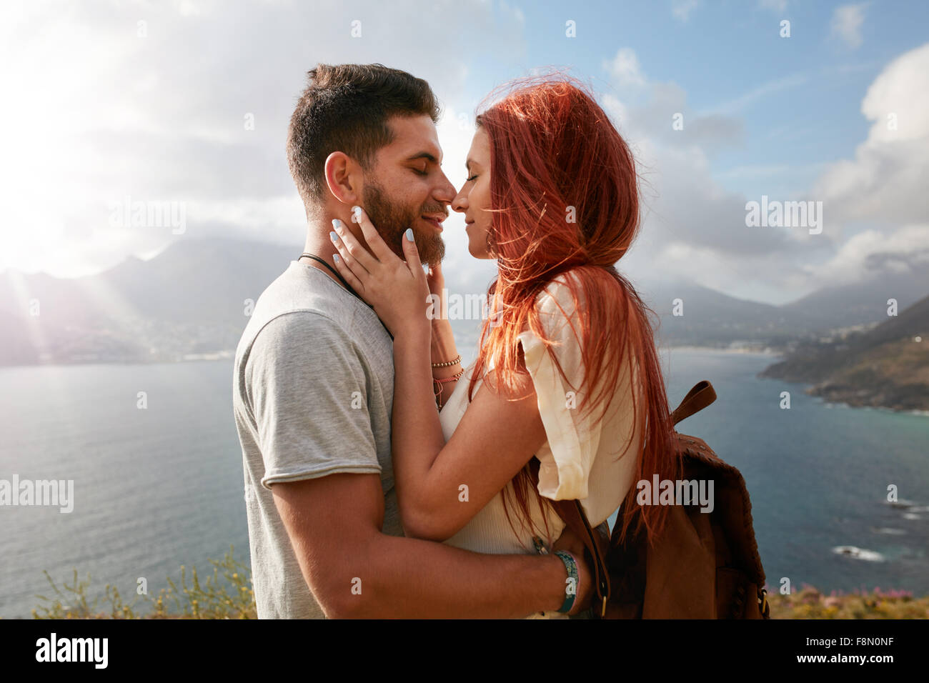 Portrait of young man and woman about to share a romantic kiss. Affectionate young couple enjoying their love in - Stock Image