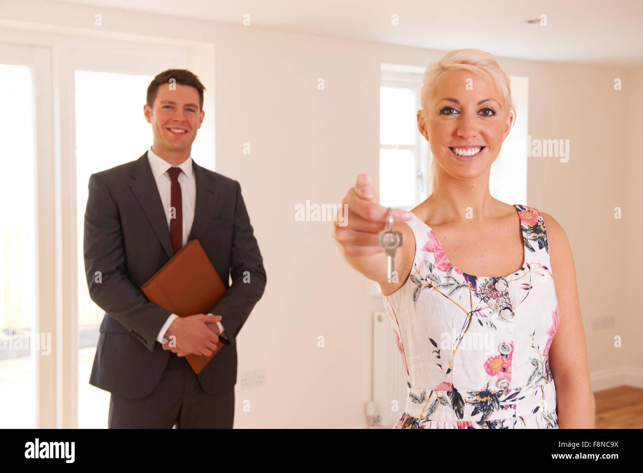 Estate Agent Handing Over Keys To Female House Buyer - Stock Image
