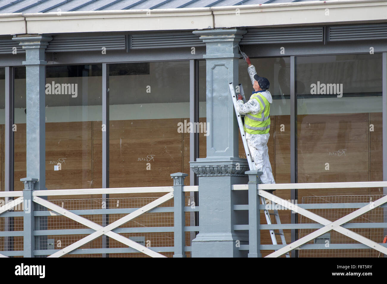 A painter painting a pillar on Town Pier in Gravesend, Kent. - Stock Image