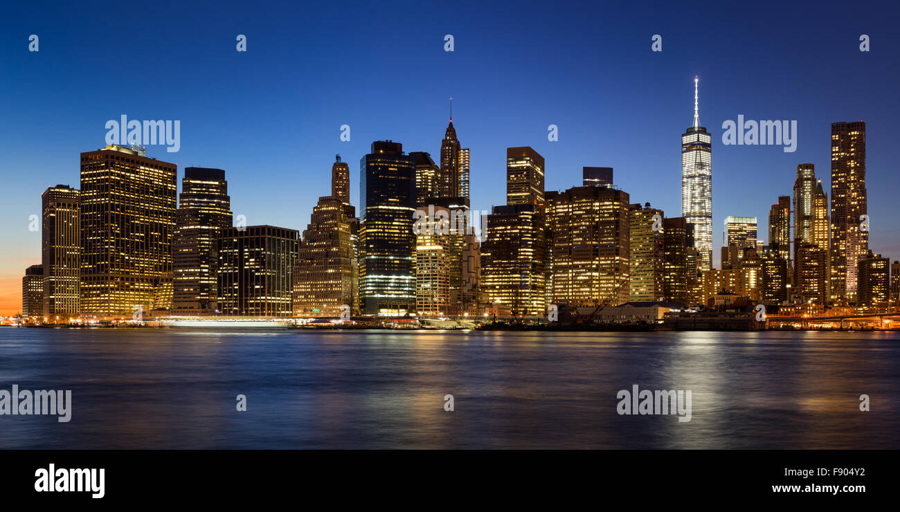 New York City skyline of Lower Manhattan Financial District at twilight with  illuminated skyscrapers rising above - Stock Image