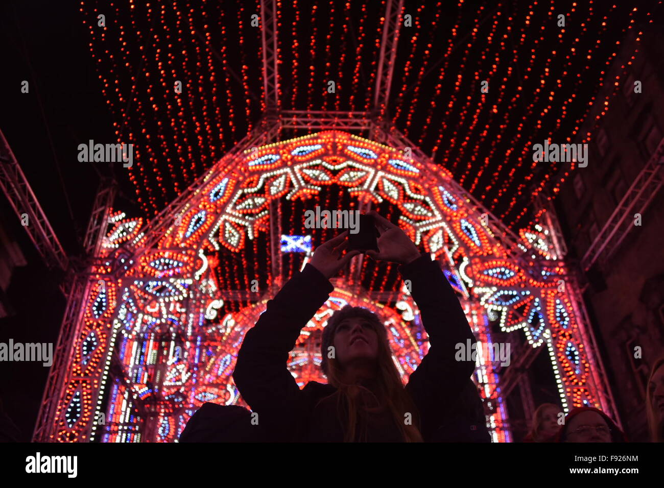 Edinburgh, Scotland, UK. 13th December, 2015. A woman takes a photograph of The Street of Light Christmas light - Stock Image