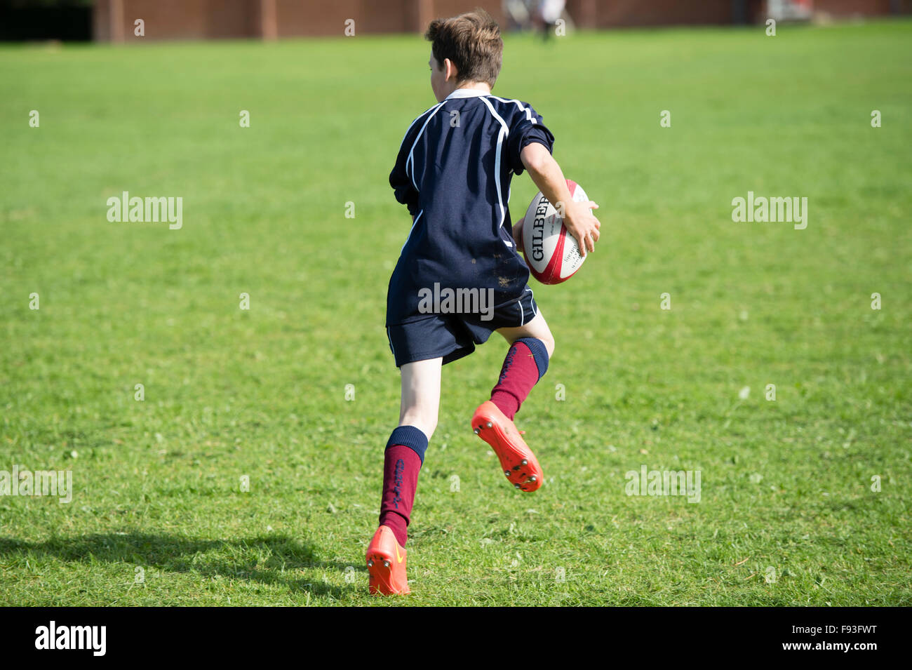 Secondary education Wales UK: physical education lesson - a teenage boy playing rugby on a school games pitch field. - Stock Image