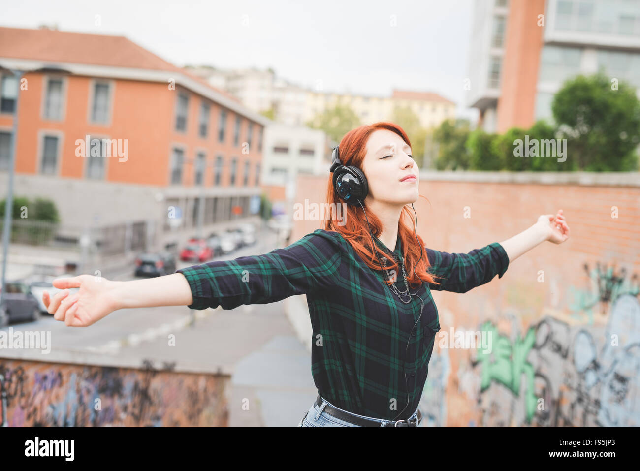 Half length of young handsome caucasian redhead straight hair woman listening music with headphones, feeling free - Stock Image