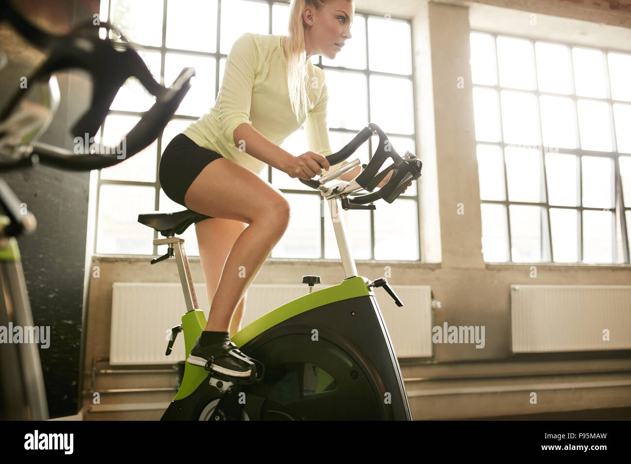 Fitness woman on bicycle doing spinning at gym. Fit young female working out on gym bike.Stock Photo